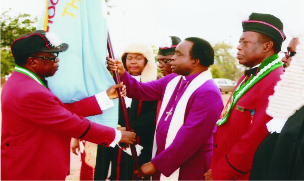 Sir Gab Oduah, President KSC Owerri receives the flag from Bishop Cyril Okorocha PhD the Superior of the Order) for the 2015 year activities of the Council of Knights, Owerri Diocese.