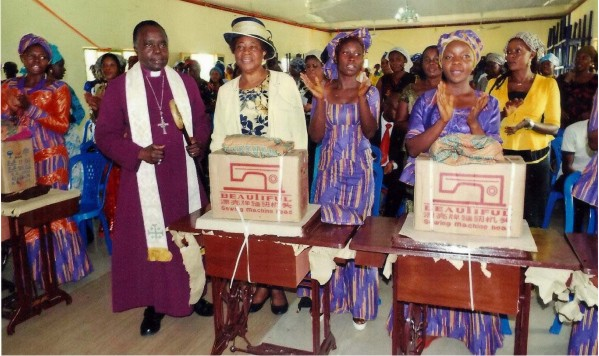 Graduands of the Women's Ministries  and the Bishop's Foundation Skills Acquisition programme, Diocese  of Owerri, with  their machines at a group photograph with the Bishop Rt Rev. Cyril C. Okorocha PhD and his wife Dr Mrs Eunice Okorocha